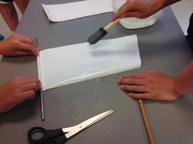 Applying glue thinned with water and a little rubbing alcohol to prevent wrinkling.One person holds the paper on the steel rolling-pin to prevent the two from getting glued together.